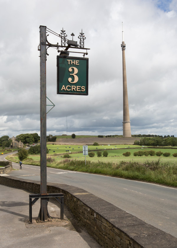 The Three acres inn sign overlooking the road