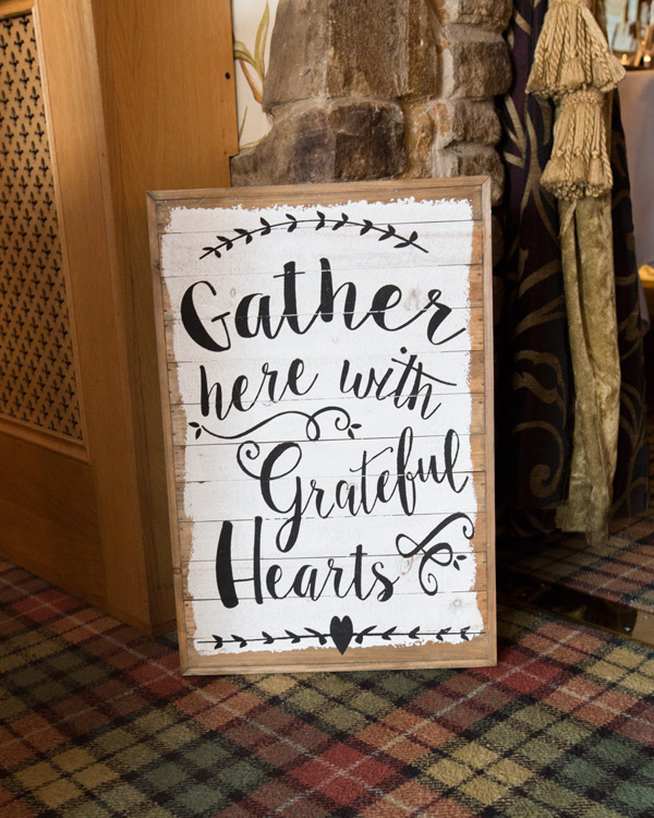 Gather here with grateful hearts wooden rustic sign outside the ceremony room at three acres inn
