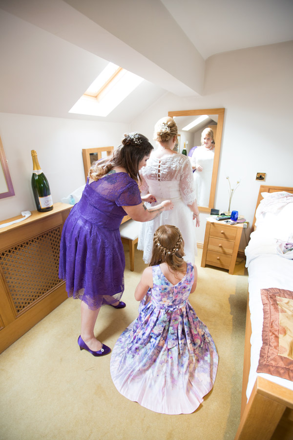 Bride looking in the mirror while the bridesmaids fasten her dress in the three acres inn bridal suite
