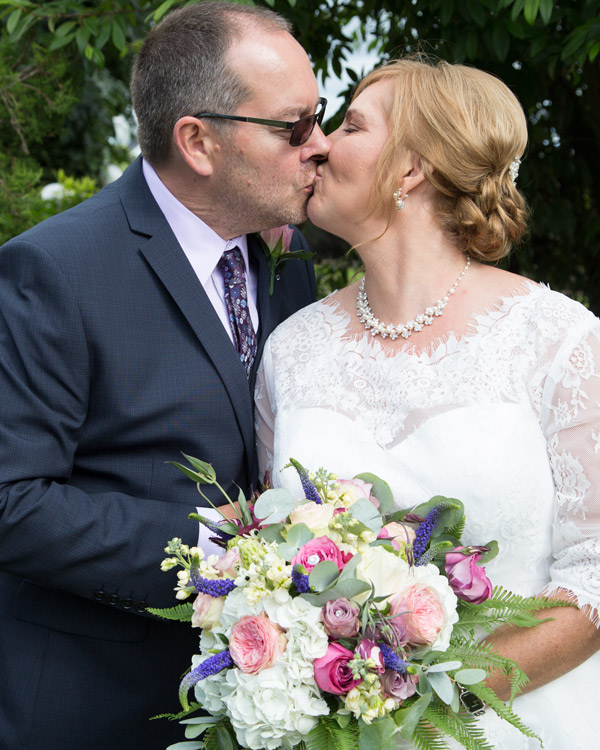 Bride and Groom kiss in the gardens of the three acres inn huddersfield