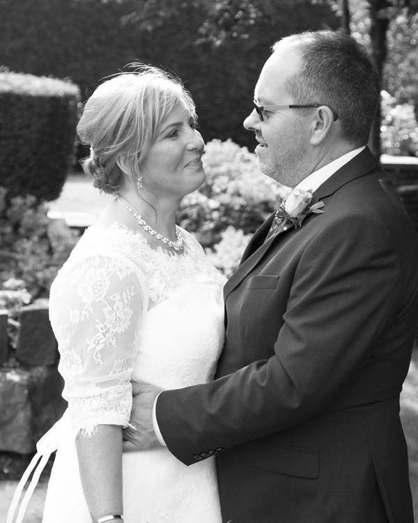 Bride and Groom looking at each other in the garden at the three acres inn huddersfield Black and White
