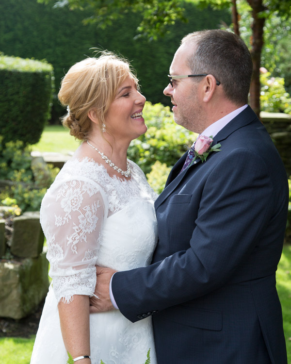 Bride and Groom looking at each other in the garden at the three acres inn huddersfield