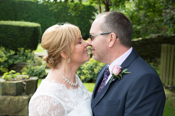 Bride and groom just before they kiss in the garden of the three acres inn