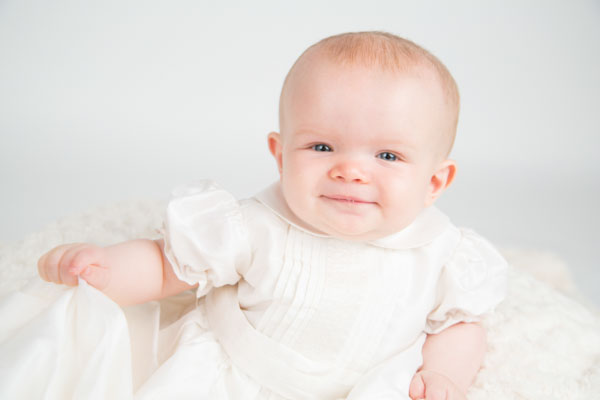 baby girl in white christening gown looking at the camera