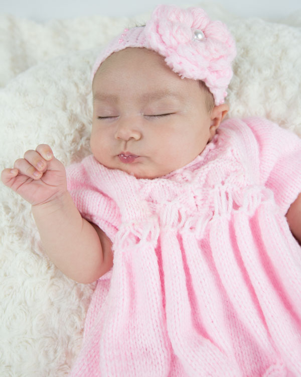 baby girl in pink crochet dress and headband sleeping on a cream blanket