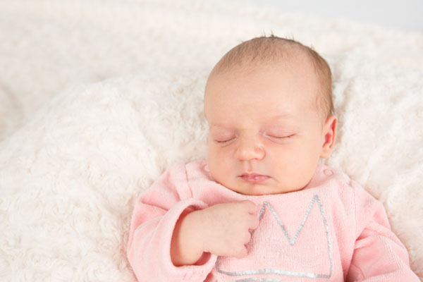 Baby girl sleeping on a blanket wearing a crown on her pink top