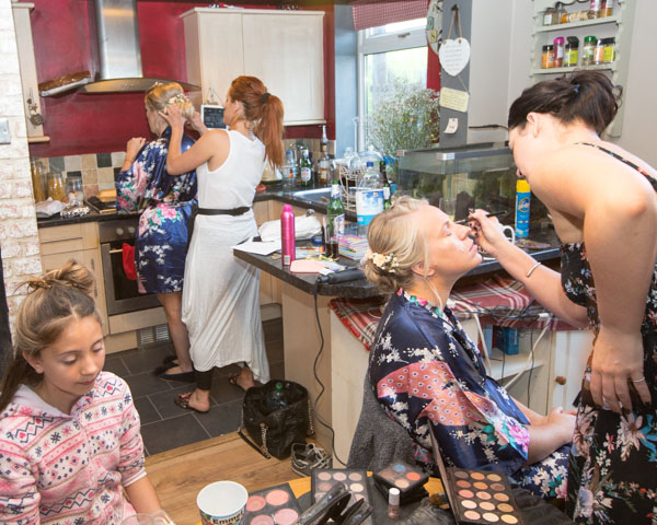 Hairdresser and makeup artist attending to bridesmaids on the morning of the wedding