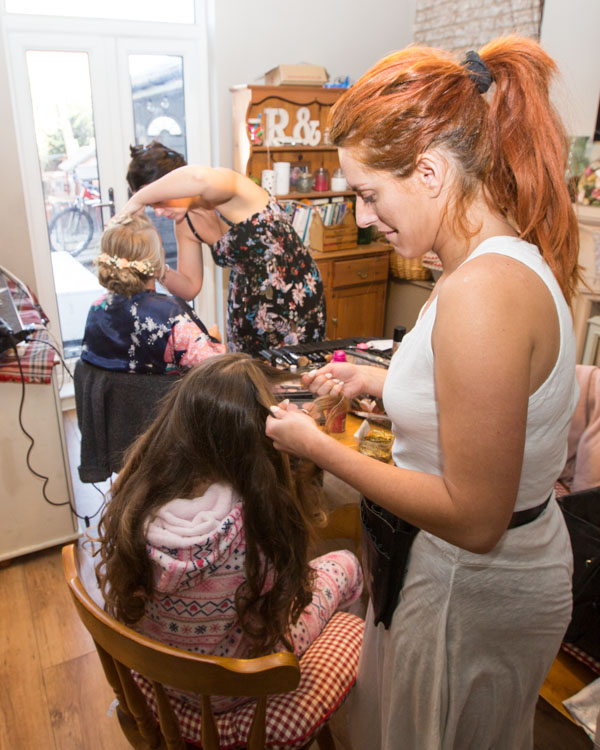 Hairdresser doing a flowergirls hair with the make up artist in the background with a bridesmaid