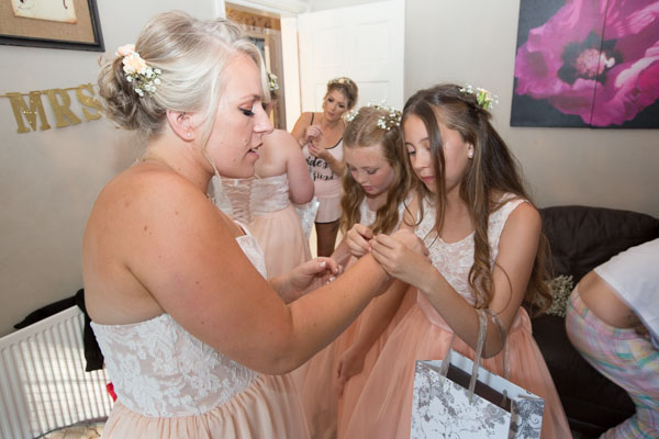Bridesmaids putting on the jewelry bought for them by the bride on the morning of the wedding