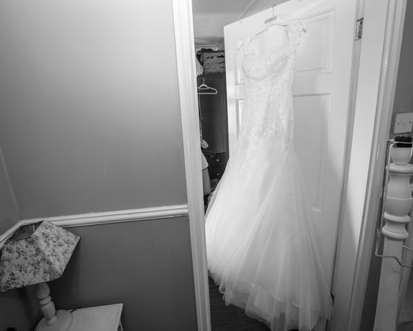 The wedding dress hung on the back of a white door in the brides house