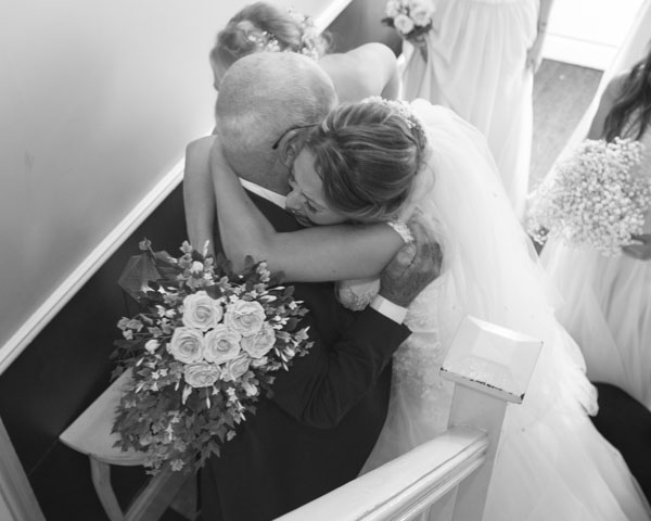 Bride hugging her Grandad at the bottom of the stairs on the morning of the wedding