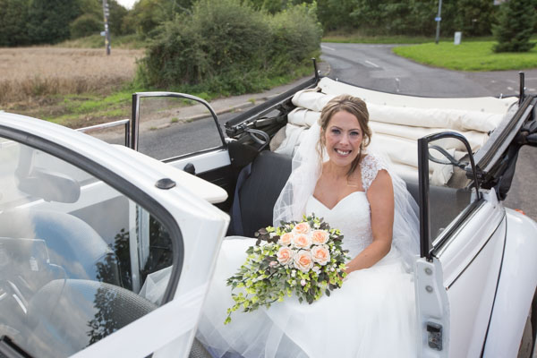 The bride arriving in a white convertible wedding car from the yorkshire wedding car company