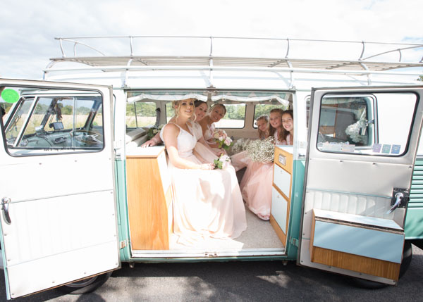 bridesmaids sitting inside a green camper van from the Yorkshire Wedding Car Company