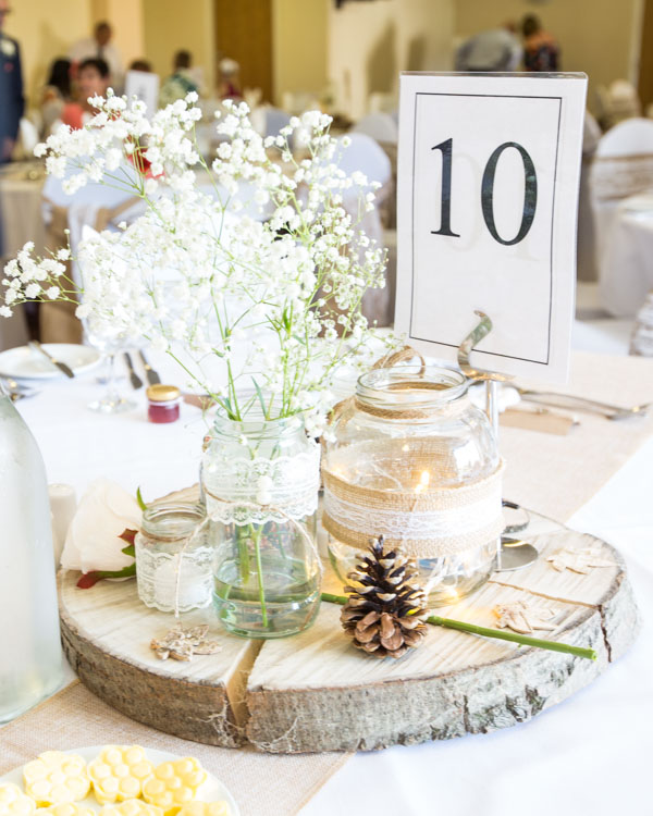 Centrepiece at Shaw Lane Sports Club of a pine cone on a wooden block with glass jars covered in lace