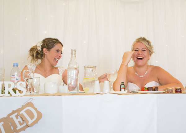 Bride and Maid of Honor laughing at the top table during the speeches