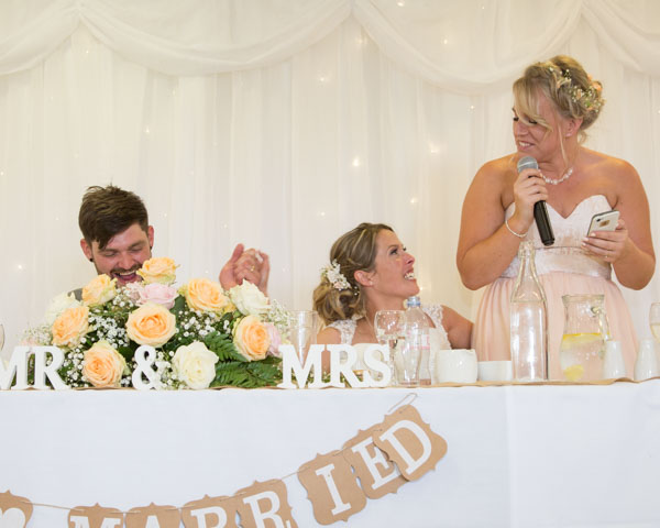 Maid of Honor giving a speech at the top table while looking at the Bride and laughing