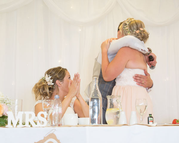Groom and Maid of Honor hugging at the top table while the Bride applauds
