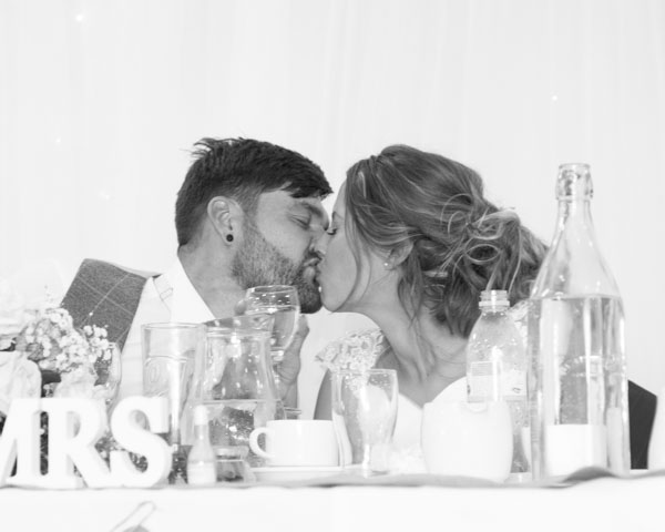 Bride and Groom kissing at the top table