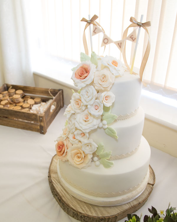 White Iced wedding cake with Love banner cake topper and pink flowers cascading down the tiers