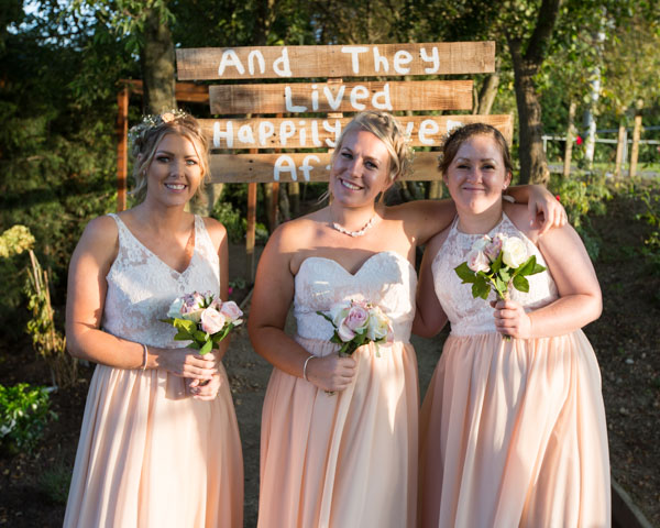 Bridesmaids standing in front of the Happily Ever after sign at Shaw Land Sports Club Barnlsey