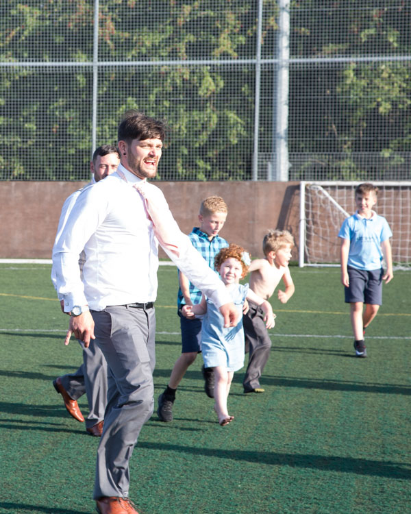 Groom and Groomsmen playing football with the children at the wedding at Shaw Lane Sports Club Barnsley