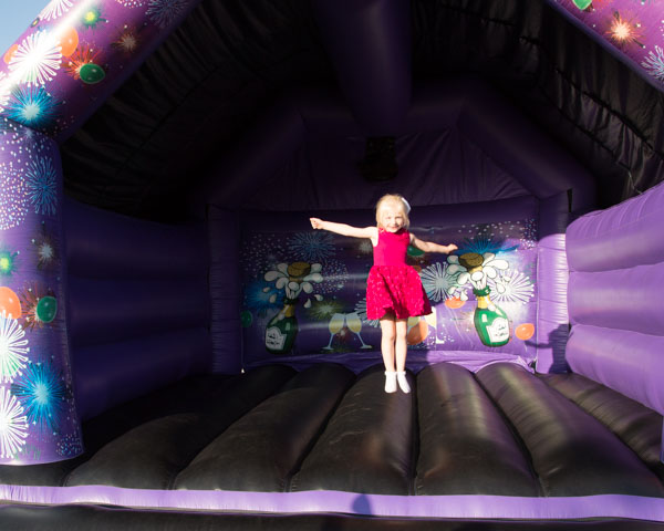 Girl in a pink dress on a purple bouncy castle at Shaw Lane Sports Club Barnsley