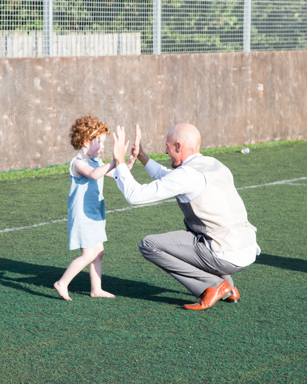Groomsman high fiveing a girl in a blue dress on the football pitch at Shaw lane Sports Club Barnlsey