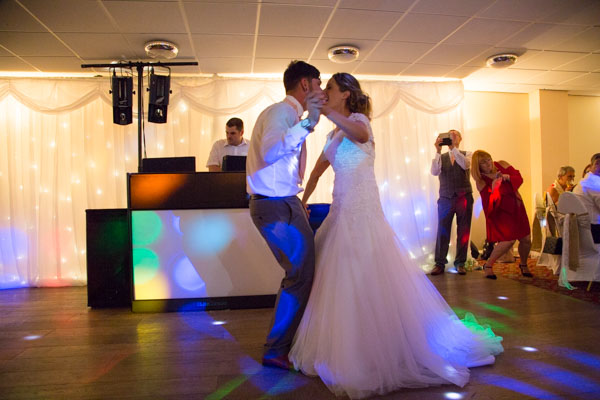 Bride and Groom doing their first dance while guests watch them
