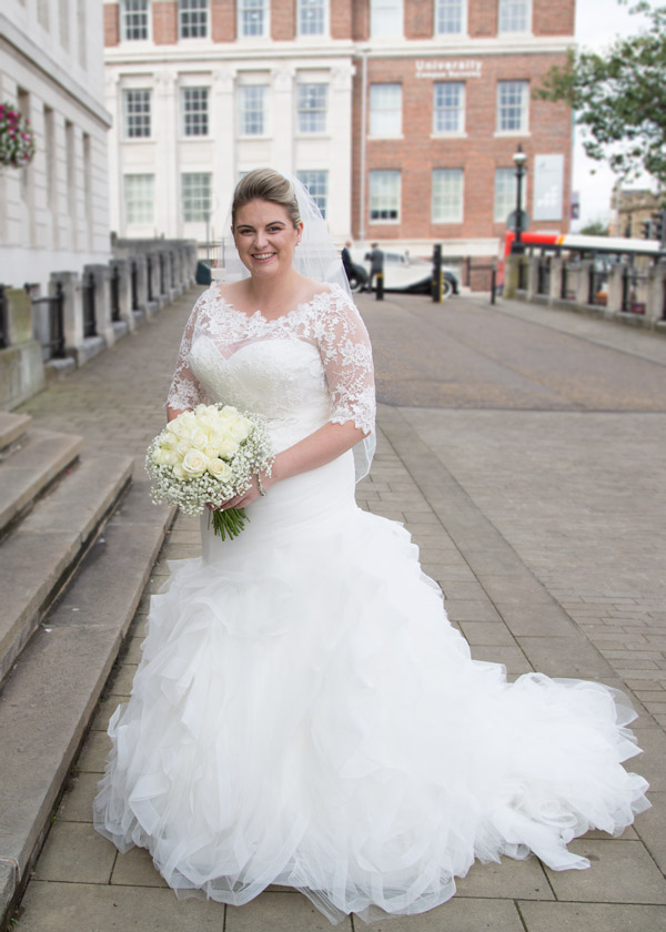 Bride standing outside Barnlsey Town Hall with her bouquet