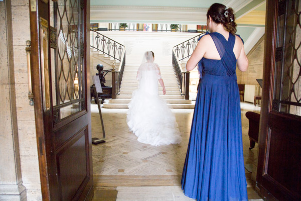 Bride in the entrance of Barnsley town hall with her Bridesmaid behind her standing in the doorway bespoke wedding photography
