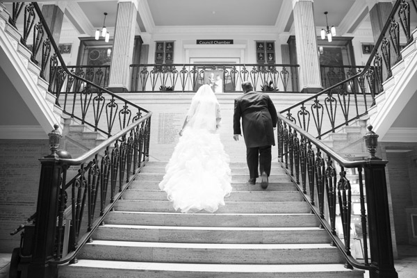 Bride and Groom walking up Barnsley Town Hall steps in black and white bespoke wedding photography