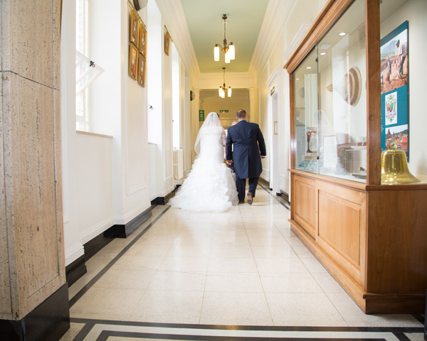 Bride and Groom walking down the corridor to the wedding ceremony room at Barnsley Town Hall
