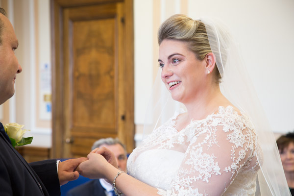 Bride placing ring on grooms finger while saying wedding vows at Barnsley Town Hall wedding