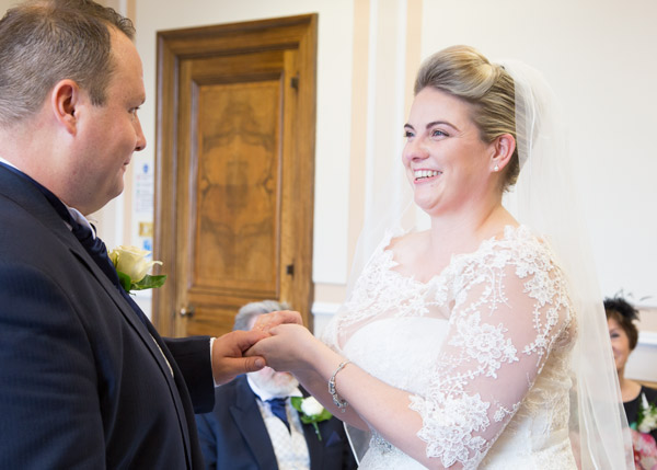 Bride laughing while placing wedding band on Grooms finger during the wedding certemony at Barnsley Town Hall bespoke wedding photography