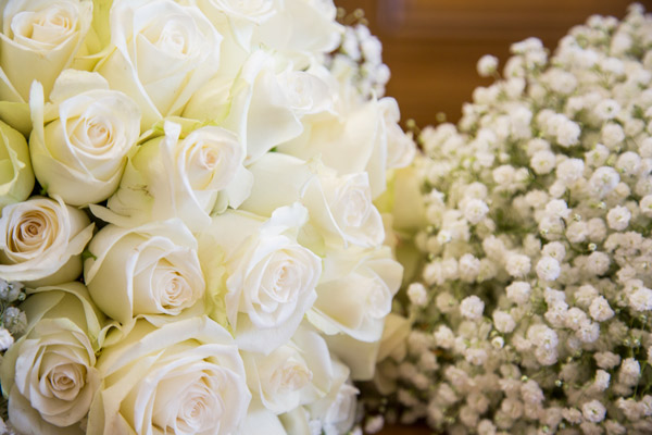Bridal bouquet of white roses and bridesmaid posy of babys breath close up with wooden backdrop