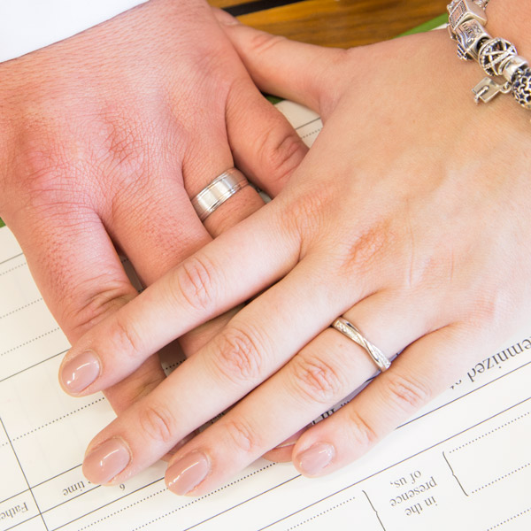 Bride and Groom ring hands on top of the wedding register