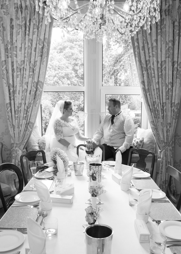 Bride and Groom in the window at Quintessential Catering on their Wedding day