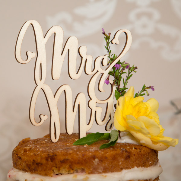 Mr & Mrs wooden cake topper on top of naked cake decorated with yellow and purple flowers