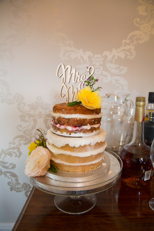 A naked wedding cake decorated with colourful flowers and wooden cake topper sitting next to the alcohol selection at Quintessential Catering Barnsley