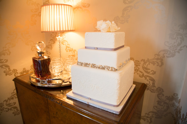 Second fake wedding cake traditionally decorated with lace detail and purple bow