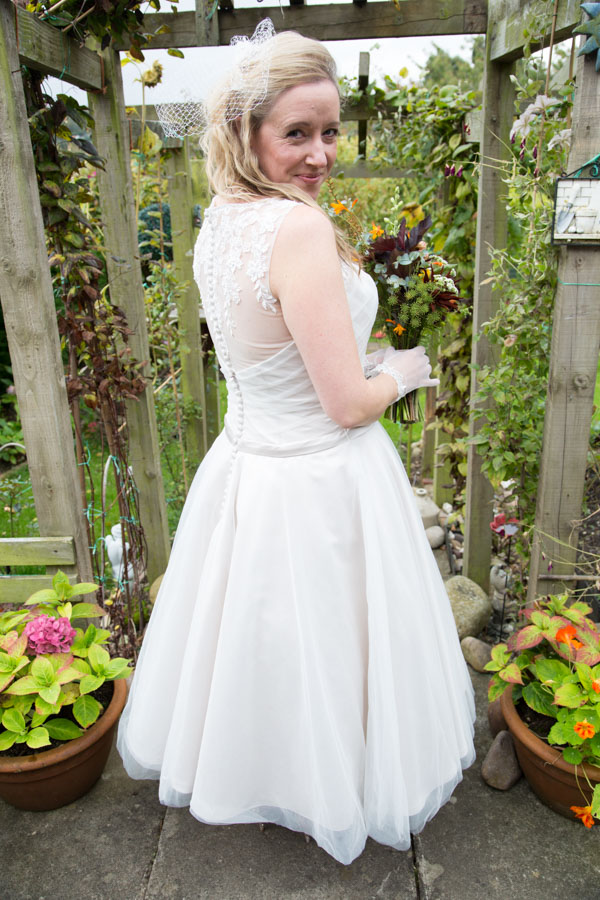 Bride looking over her shoulder in her garden before her wedding ceremony
