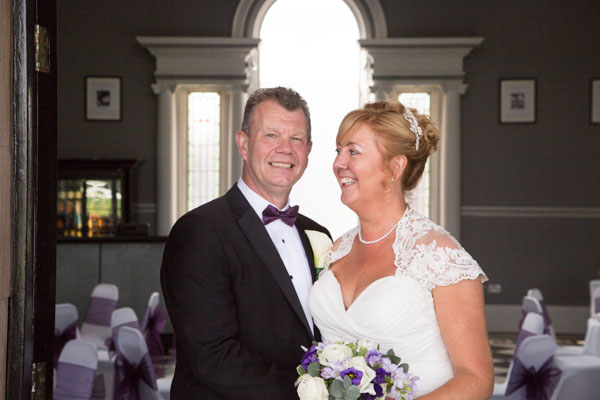 Bride and Groom laughing at Old weighing room at Doncaster Racecourse Wedding