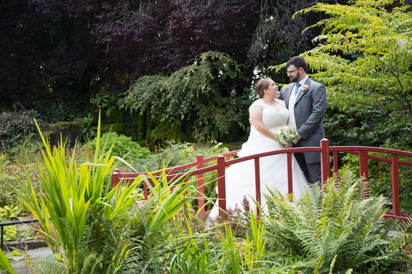 Bride and groom standing on a bridge and looking at each other during Chester Zoo wedding