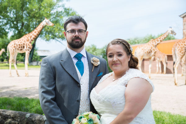 Bride and groom looking at the camera in front of the giraffe enclosure at Chester Zoo