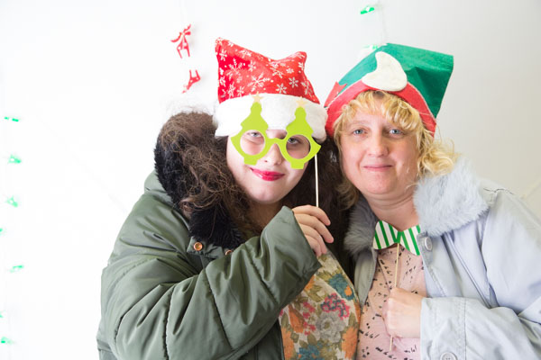 Two ladies using Christmas props in a festive photobooth