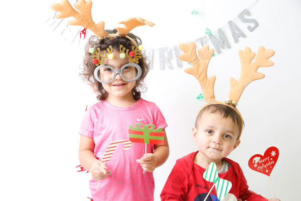 Two Children using Christmas props in a festive photobooth