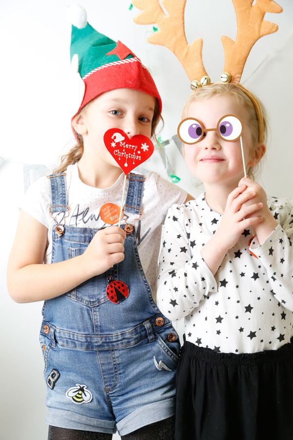 Two girls dressing up in a Christmas Photoboth