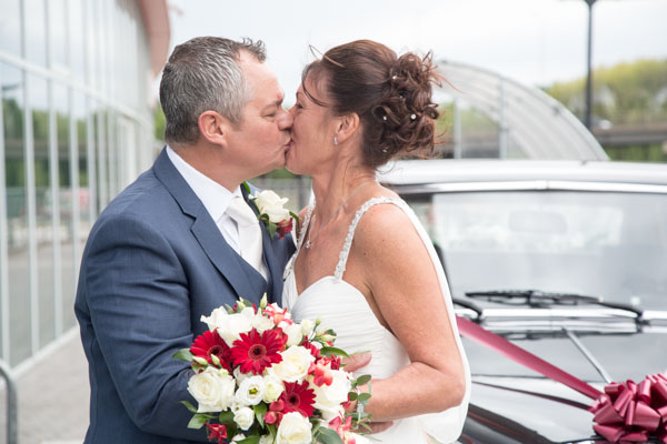 Bride and Groom kissing in front of the wedding car at New York Stadium Rotherham