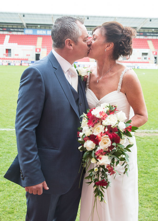 Bride and groom kissing at New York Stadium football ground