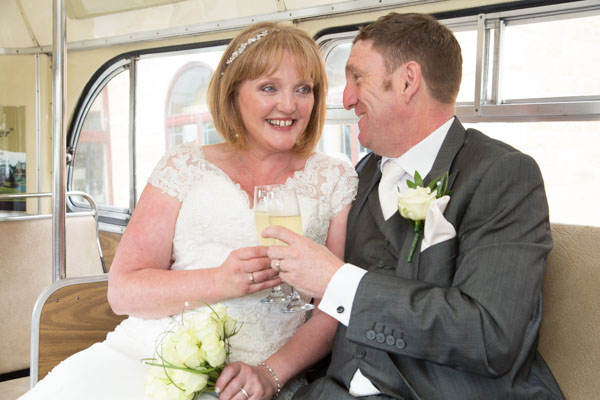 Bride and Groom drinking champagne in a green wedding bus